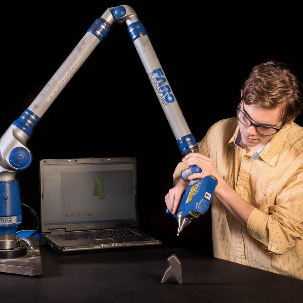 Worker using robotic arm.